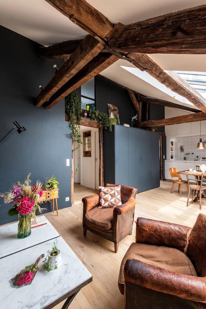 poutres apparentes murs armories gris anthracite parquet bois cuisine et credence carrelage blanc chaises tissu et cuir table basse de marbre