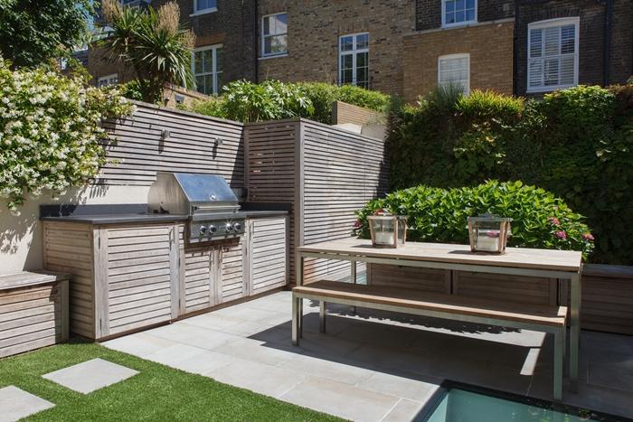 projet transformation jardin en cuisine d été en bois équipement inox revêtement mural clôture bois panneaux plan de travail gris anthracite