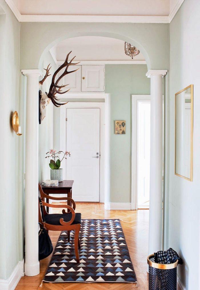 quelle couleur pour un couloir d entrée murs vert pastel colonnes blanches parquet clair tapis geometrique chaise bois et noir deco murale originale