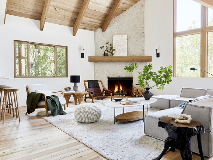 salon blanc et bois avec accents en noir cheminée plafond poutres bois revêtement parquet bois clair tapis moelleux blanc pouf crochet blanc tabourets de bar bois fauteuil blanc et bois plaid vert foncé