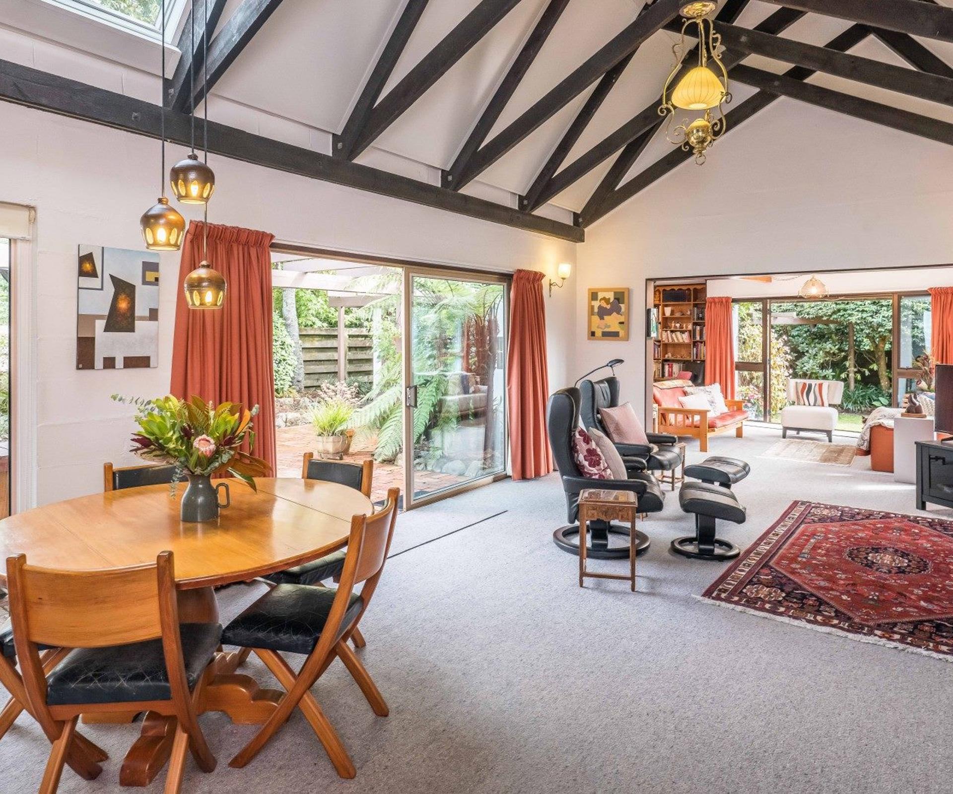 salon ouvert sur salle à manger avec table ronde et chaises bois et cuir fauteuils en cuir tapis boheme coloré rideaux organge