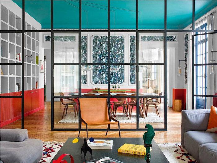 séparation salon salle à manger dans deco appartement haussmannien avec meubles rouge et blanc table salle à manger marbre entourée de chaises de bois canapés gris autour d une table bois foncé