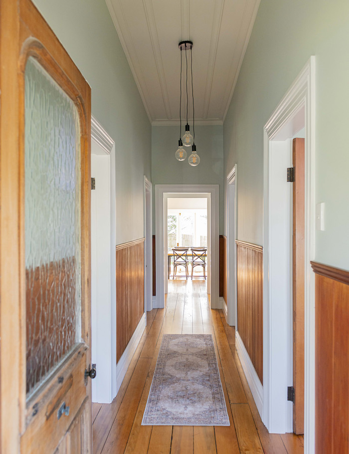soubassement de bois et peinture couloir etroit vert celadon pastel clair patquet bois vlond usé petit tapis vintage