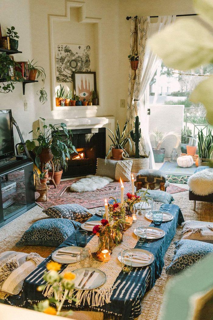 style deco boheme chic de salon boheme avec table basse coussins d assise au sol cheminée noire moderne tapis colorés plusieurs plantes en pots style jungle urbaine