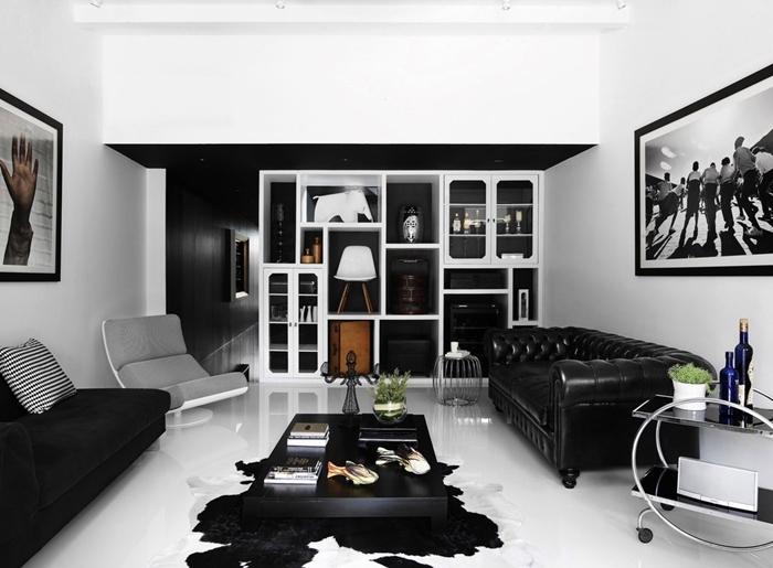 table basse noire tapis imitation peau animale canapé noir velours mat peinture noir et blanc art mural bibliothèque blanche