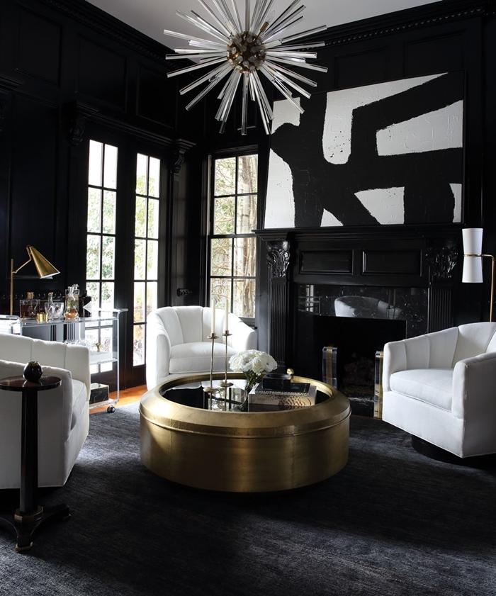 table basse ronde en or et verre tableau noir et blanc abstrait salon noir et blanc avec cheminée fauteuiles blancs parquet bois