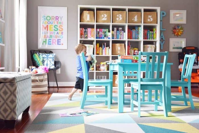 table et chaises pret de l etagere avec les jouets endant tapis geometrique belles couleursidée déco salle de jeux meuble de rangement jouet simplicité