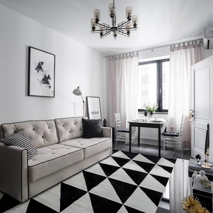 tableau noir et blanc décoration murale minimaliste style intérieur canapé boutonné beige coussin gris anthracite tapis blanc et noir motifs triangulaires