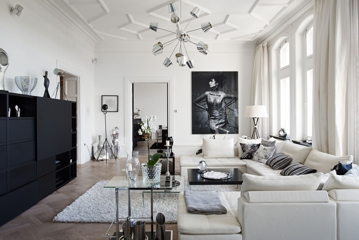 tableau noir et blanc décoration salon style épuré meuble noir mat sans poignée tapis moelleux blanc revêtement sol bois