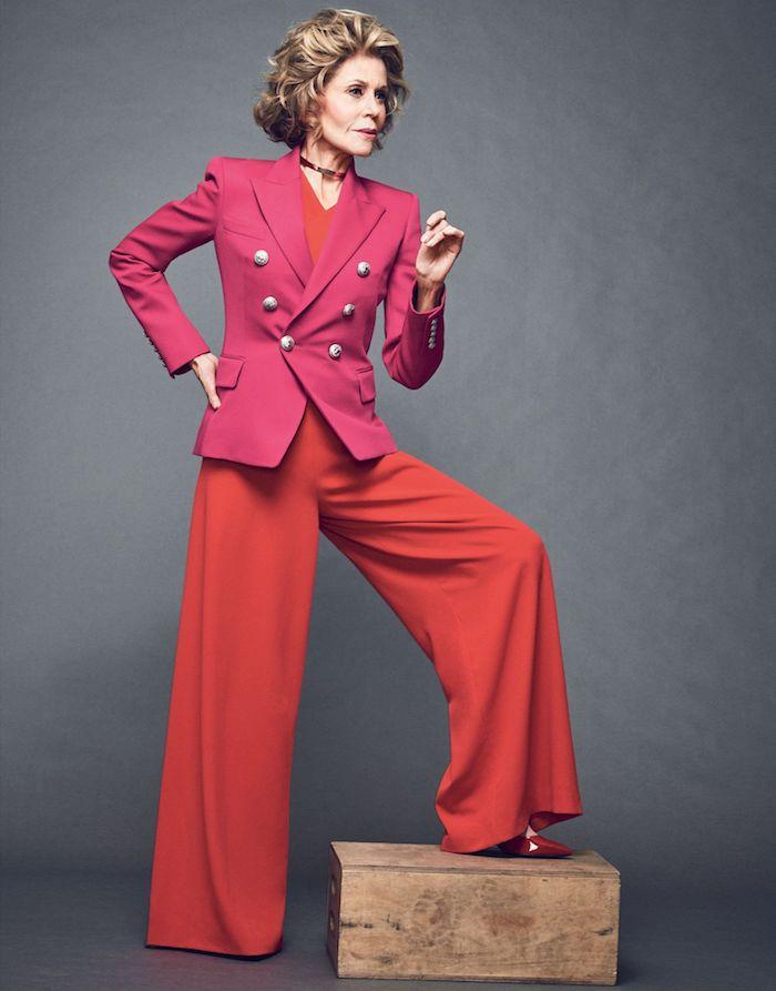 tenue avec pantalon évasé et top rouge et une veste de couleur rose cheveux bouclés coupe de cheveux femme 60 ans carré ondulé