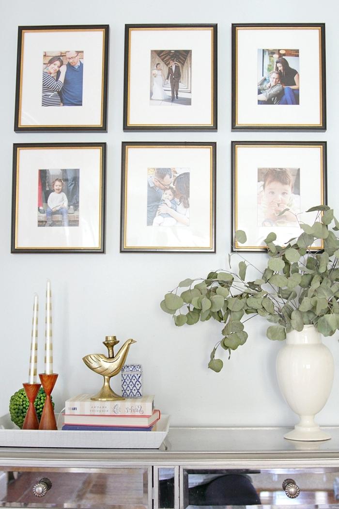 vase blanc bouquet plante verte deco murale salon livres bougeoir or commode blanc et verre mur photos famille cadre noir