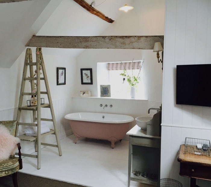 échelle décorative bois décoration sous combles chambre avec salle de bain baignoire rose et blanc chaise coussin fausse fourrure rose pastel