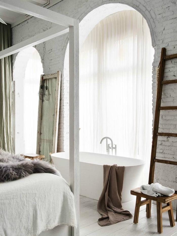 échelle décorative bois tabouret baignoire dans chambre décoration mur briques blanches cadre de lit bois blanc plaid fausse fourrure grise