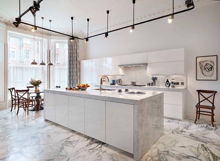 éclairage industriel moderne rail lampe noire plan de travail effet marbre sol agencement cuisine ouverte avec coin repas