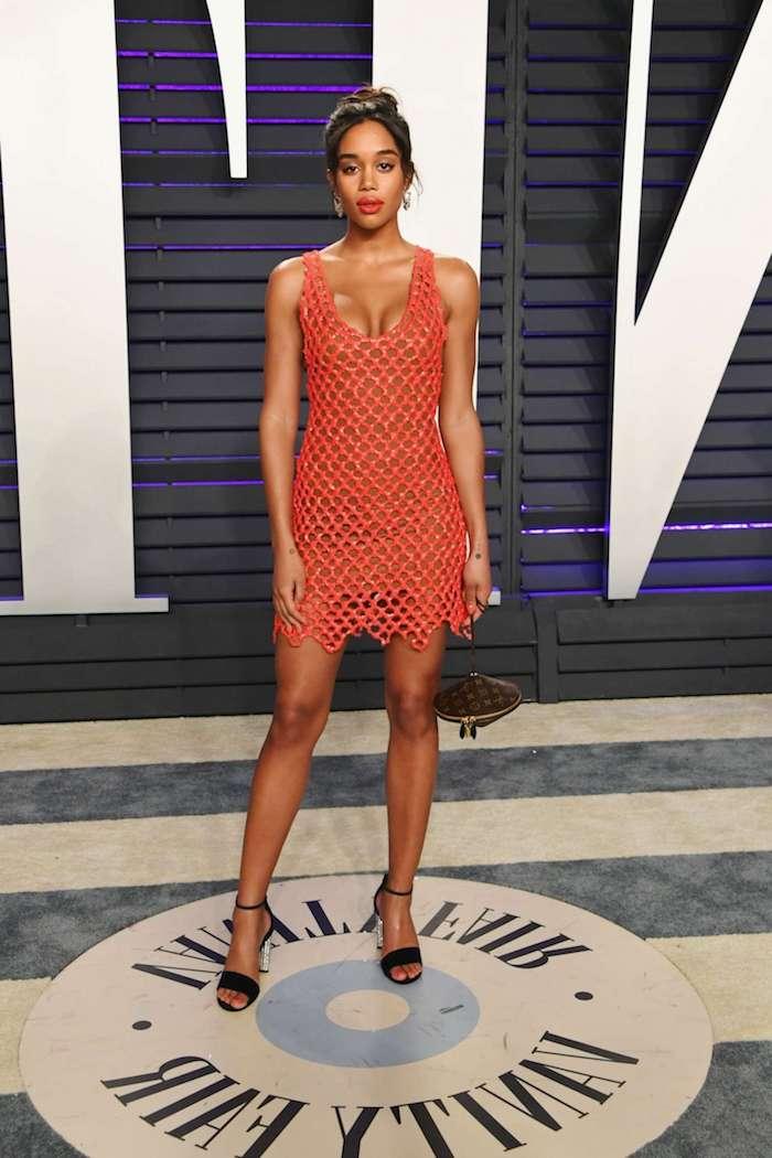 laura harrier 2019 vanity fair robe orange meches avec des sandales noires à talon et un chignon