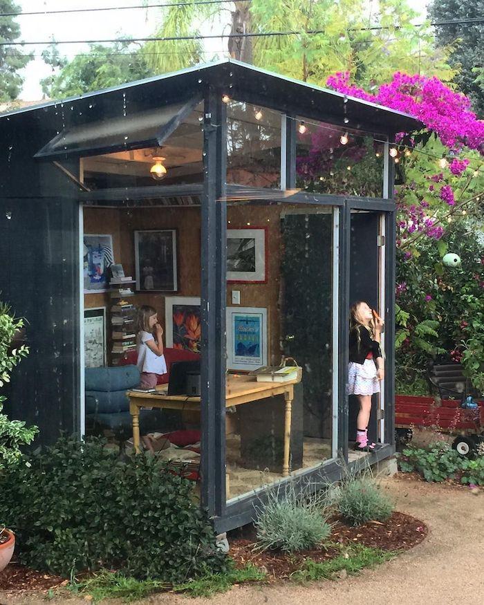 abri de jardin 15m2 entoure de verdure deux enfants dans une cabane sous la pluie