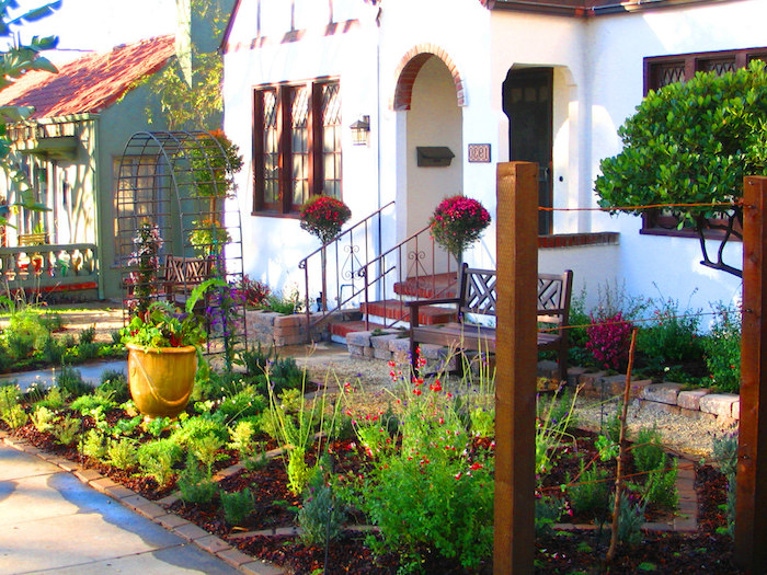aménagement cour exterieur maison blache en style provencal precedee d un jardin des plantes vertes et d un banc en bois