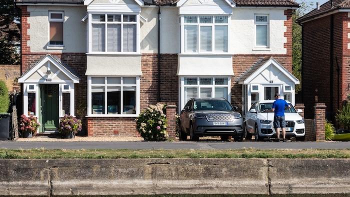 aménagement exterieur maison individuelle avec parking et des arbustes de magnolias deux voitures devant l'immobilier en tuiles