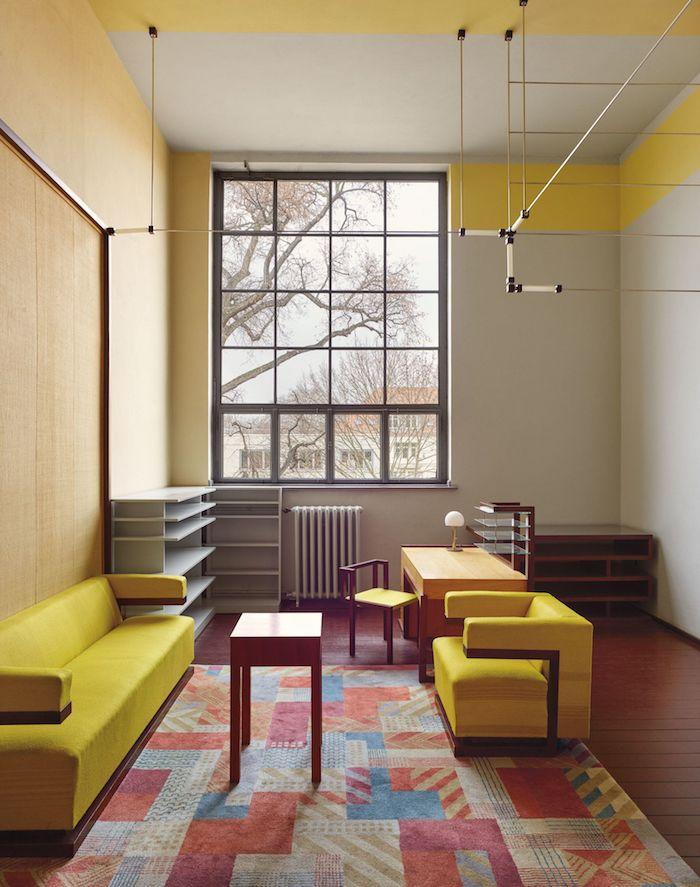 amenagement de bureau en style bauhaus des canapes jaunes et un tapis multicolore entoures des etageres originales