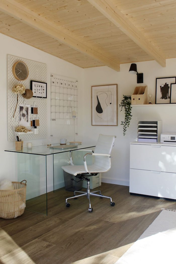 amenagement de bureau en style scandinave avec des murs blanches table en verre et plafond en bois