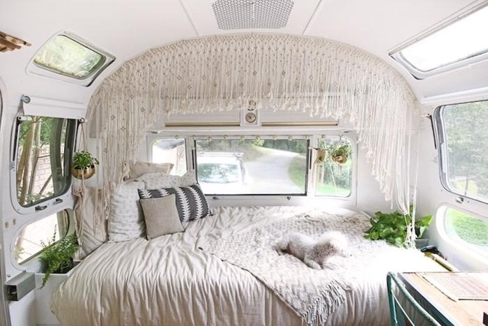 amenager son fourgon décoration bohème hippie chic jeté lit blanc coussins décoratifs rideaux macramé plantes vertes