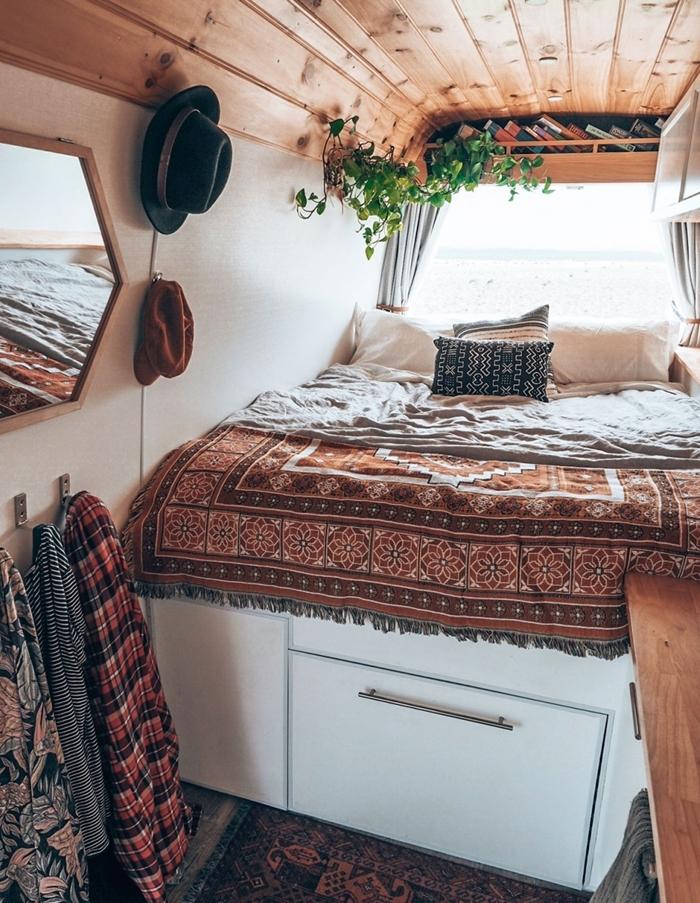 amenager son fourgon de style hippie chic jeté de lit franges motifs ethniques coussin noir miroir chapeau plafond bois