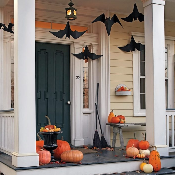 araignées de papier suspendus du plafond balais decoratifs et courges halloween et des feuilles morts sur le sol