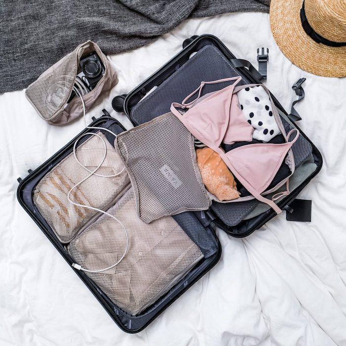 astuces rangement des cubes pour voyages valise bleue pose sur un lit