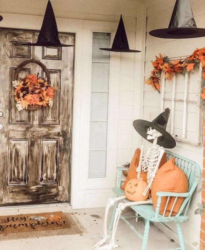 banc de bois avec squelette et des coussins de couleur orange porte bois brut guirlande de feuilles mortes chapeaux sorciere suspendues