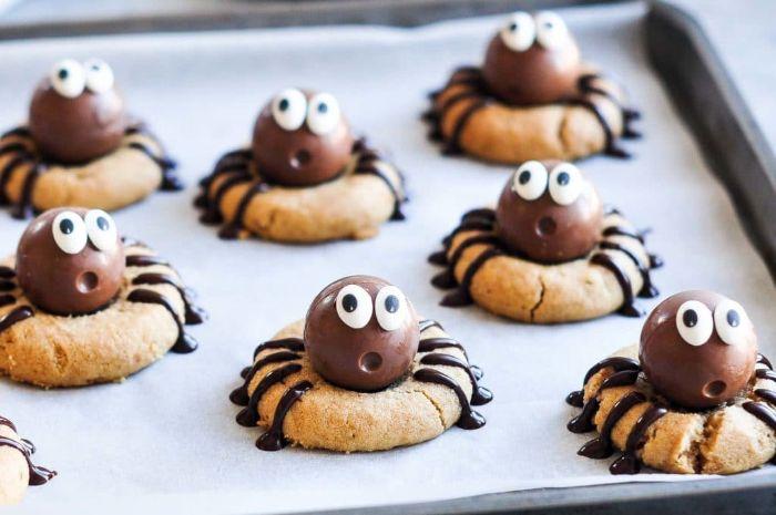 biscuit halloween au beurre de cacahuete avec bonbons dessus motif araignée aux yaux mobiles petit gateau simple