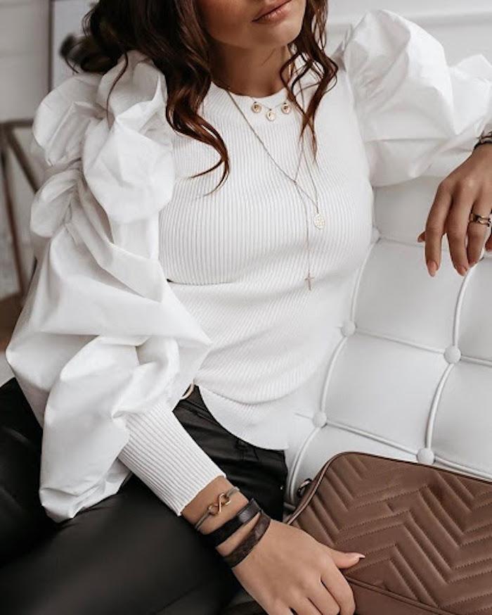 blouse manche bouffante de tissu a mailles tricotees reps des bracelets autour de la poignet sur un canape blanc en cuir