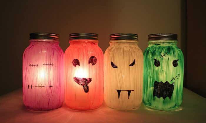 bocaux en verre repeints de peinture avec de smotifs monstre citrouille dessinés et bougies pour creer une deco halloween a faire soi meme terrifiante