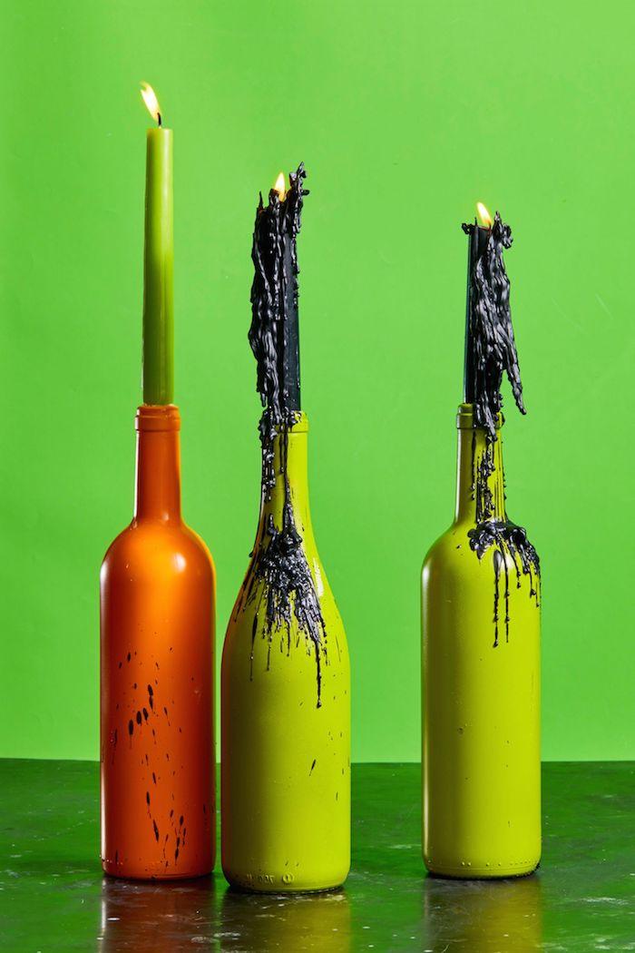 bougeoirs halloween dans bouteilles de verre recyclées repeintes avec de la cire de bougies noire