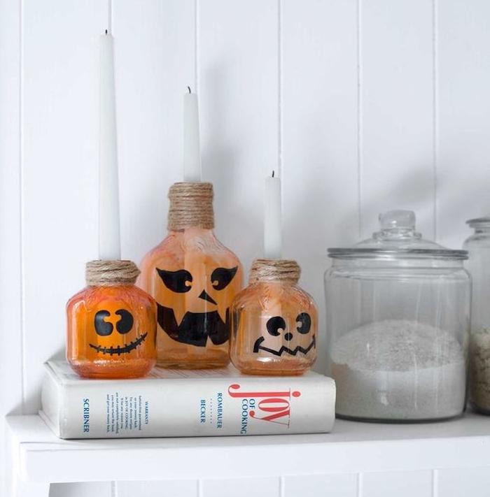 bouteilles d everre rpeint de peinture orange semi transparente avec motif citrouille jack o lantern et ficelle de chanvre autour du col deco halloween facile a faire