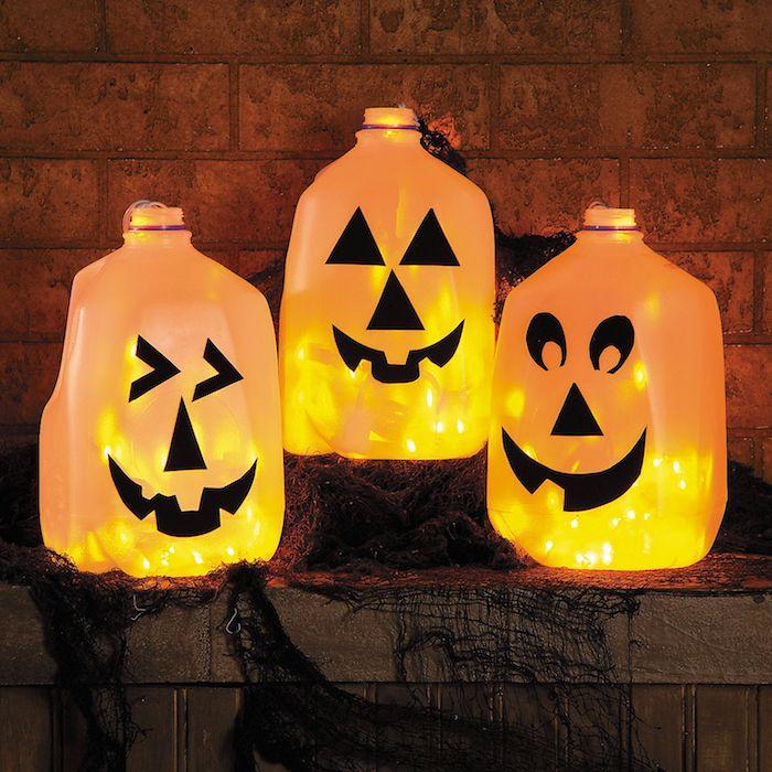bouteilles de jus lait recyclées avec des guirlandes lumineuses a l interieur et motif jack o lantern d;ecoration halloween à fabriquer