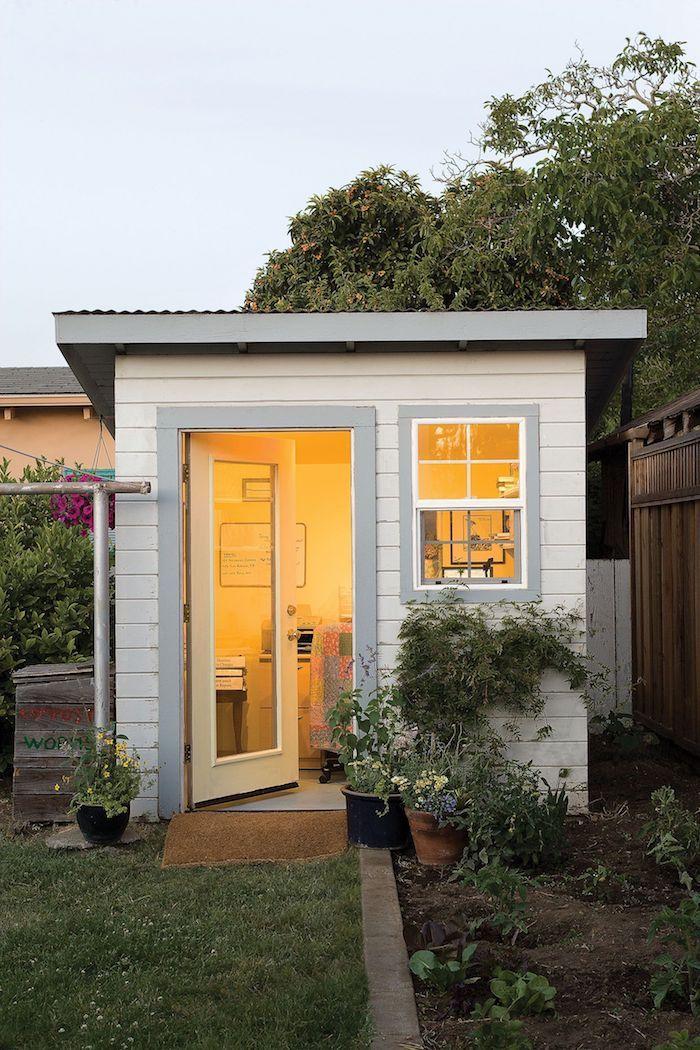 bureau de jardin petit ediffice illumine entouree des plants vertes construit en bois blanche