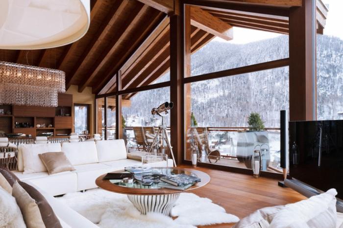 chalet dans la montagne belle vue enneigée table ronde tapis shaggy canapé blanc deco cocooning salon chaleureux canapé cosy