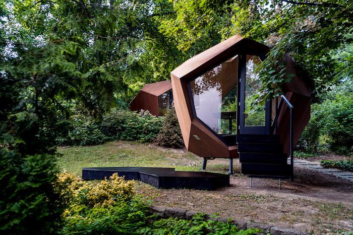 chalet en bois 20m2 devant maison avec une forme futuristique hexagonale edifice moderne