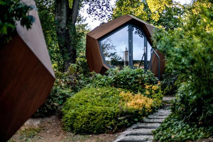 chalet en bois 20m2 en forme futuristique entoure de verdure dans la coure devant maison
