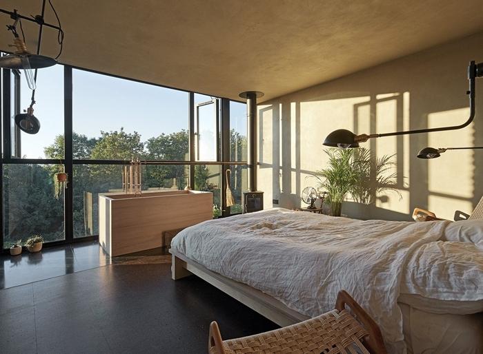 chambre avec salle de bain design intérieur cocooning peinture à effet béton meubles bois clair chaise relax lampe noir mat