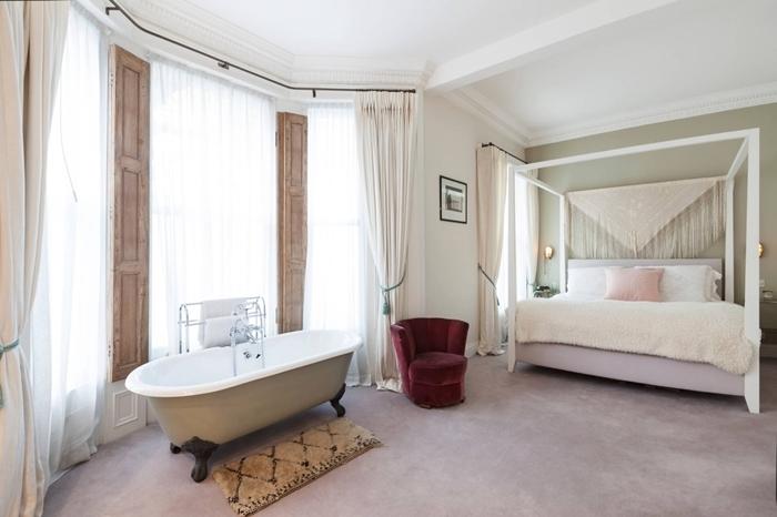 chambre avec salle de bain rideaux blancs tête de lit macramé cadre de lit blanc coussin rose pastel fauteuil velours bordeaux