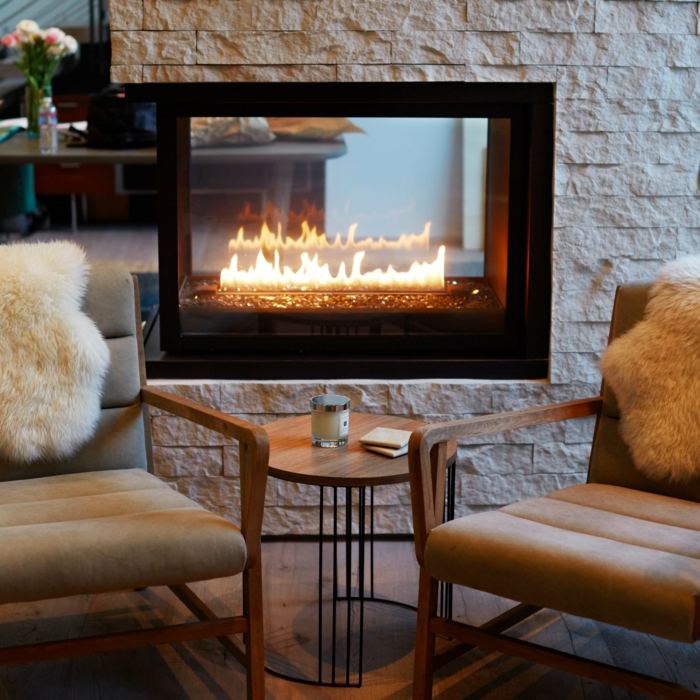cheminée allumée magnifique salon chaleureux canapé cocooning intérieur moderne fauteuils annee 60 style retro cosy