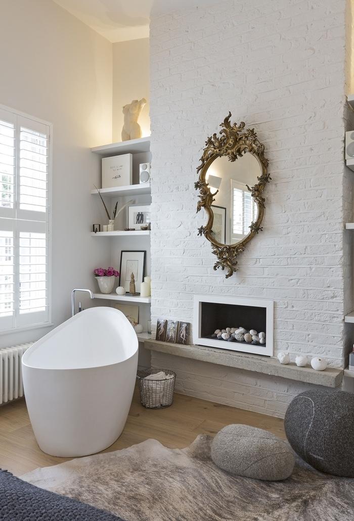 cheminée décorative revêtement briques blanches rangement mural étagère blanche suite parentale salle de bain pouf