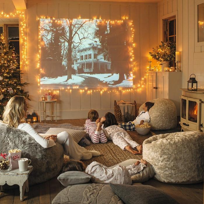 cinéma a la maison noel deco deco salon cosy inspiration déco cocooning guirlande lumineuse mere et trois enfants poufs confortables