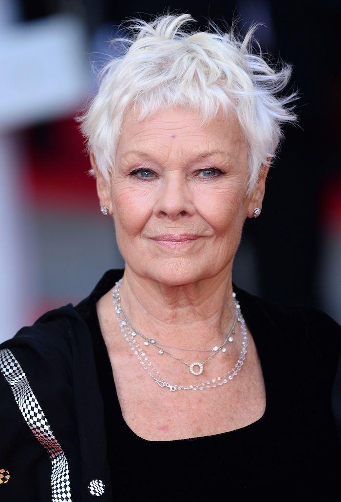 coiffure femme 60 ans épanouie femme avec un pull rose et cheveux blondes platinees