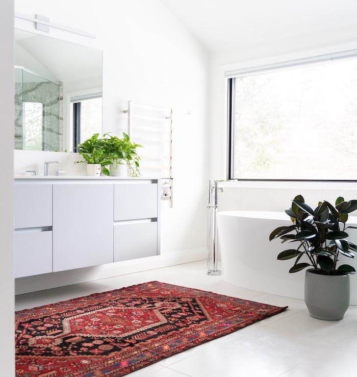 comment aménager une salle de bain cocooning blanche aux accents verts et tapis oriental coloré grand miroir rectangulaire