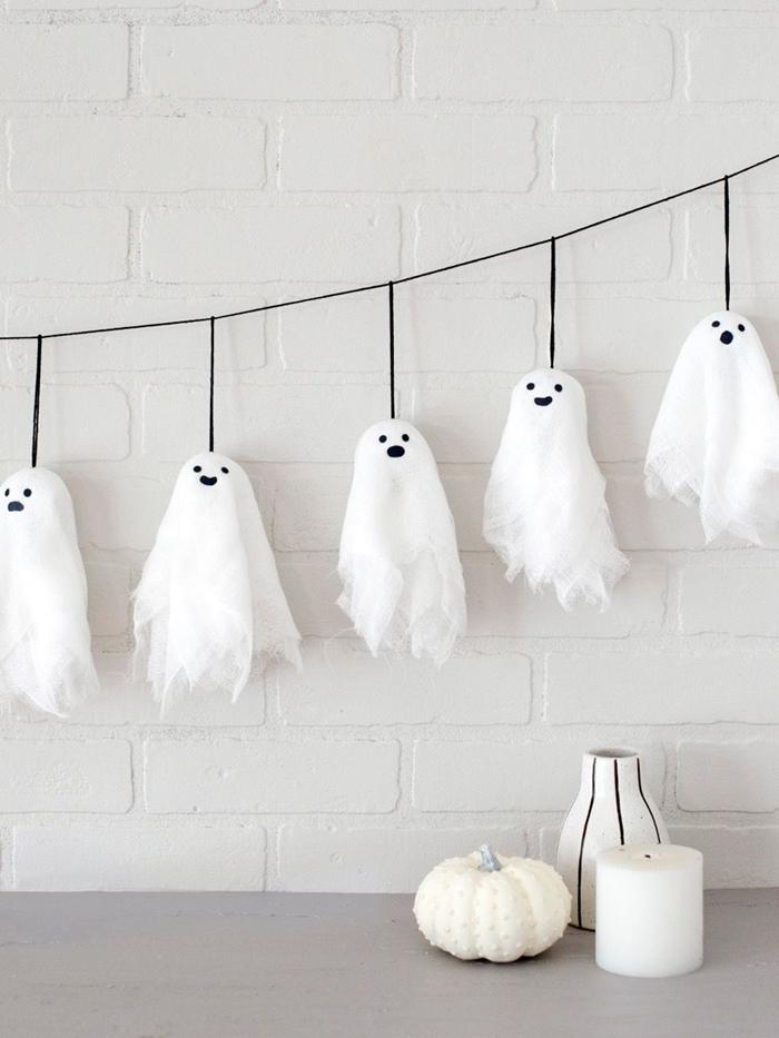 comment faire guirlande halloween facile avec fantôme fil noir petite citrouille blanche vase bougie blanche mur briques blanches