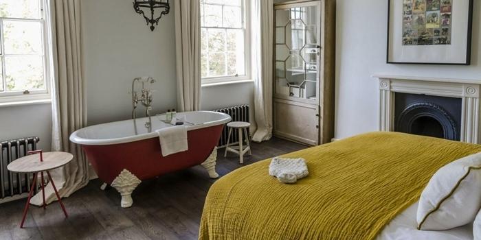 déco appartement parisien salle de bain dans chambre revêtement parquet bois foncé table café bois et métal couverture de lit jaune moutarde