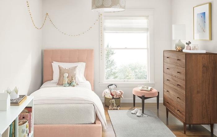 déco chambre blanche enfant lit avec tete de lit boutonnée en rose pastel meuble commode bois foncé revêtement de sol bois