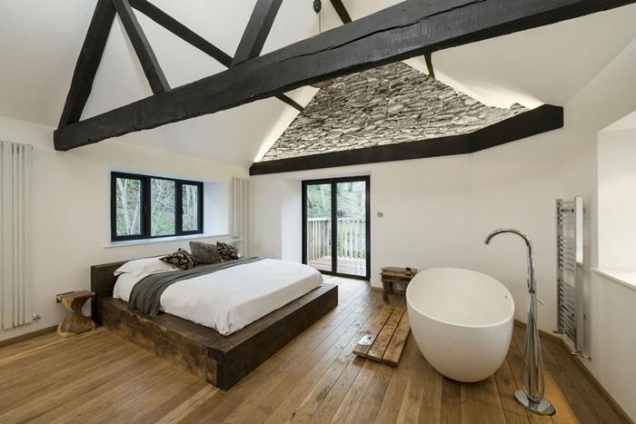 décoration chambre avec salle de bain ouverte parquet bois baignoire autoportante plafond blanc avec poutres bois noir